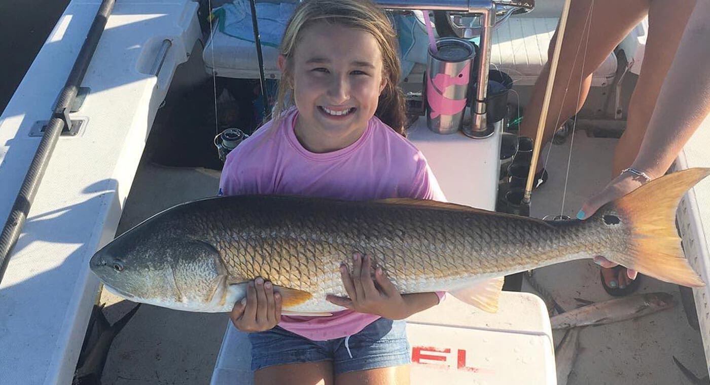 Girl holding redfish at the River Fishing Charter in Cocoa Beach