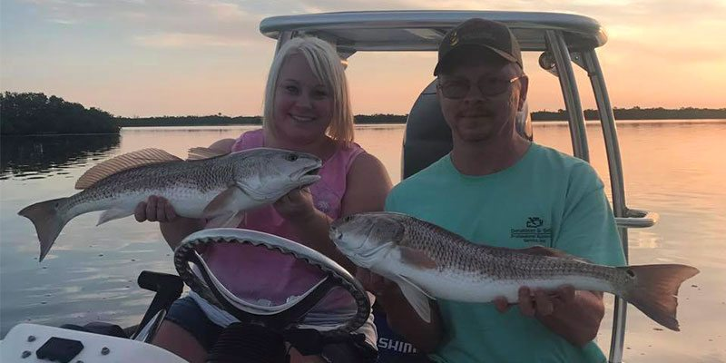 A Couple on a River Fishing Charter Holding Redfish in Port Canaveral