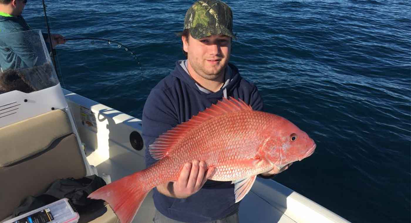 Man Holding Red Snapper at the Cape Canaveral Red Snapper Fishing Charter