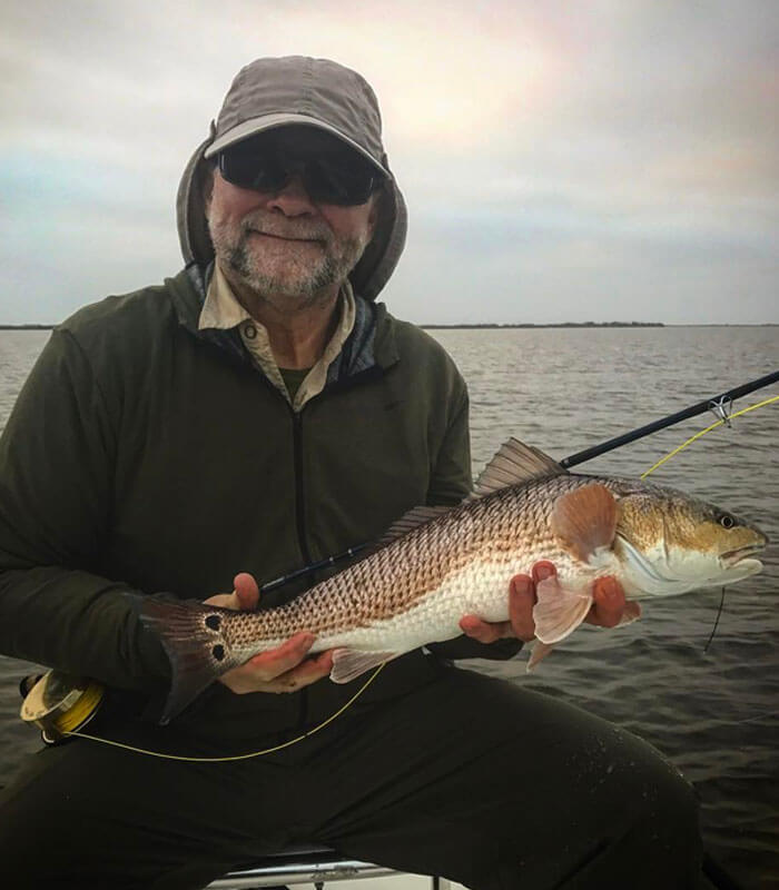 Man holding redfish at the River Fishing Charter in Cocoa Beach