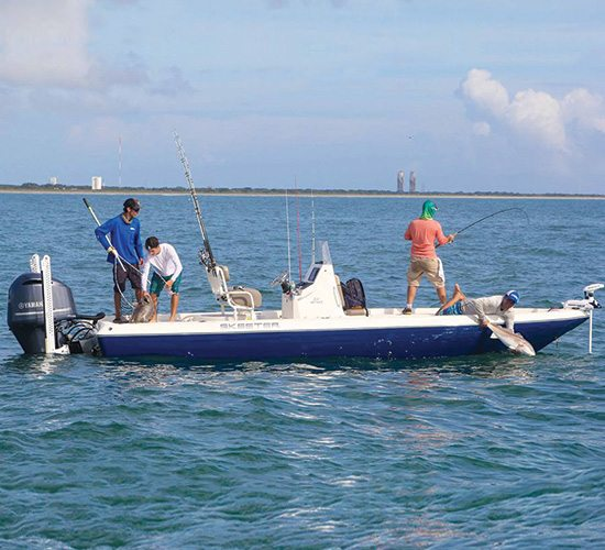 10 things to do on space coast of Florida, four men on a boat in the ocean reeling in a fish