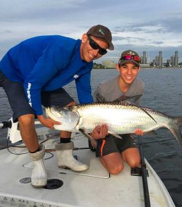 Orlando bucket list, captain and boy holding large caught Tarpon on bow of boat
