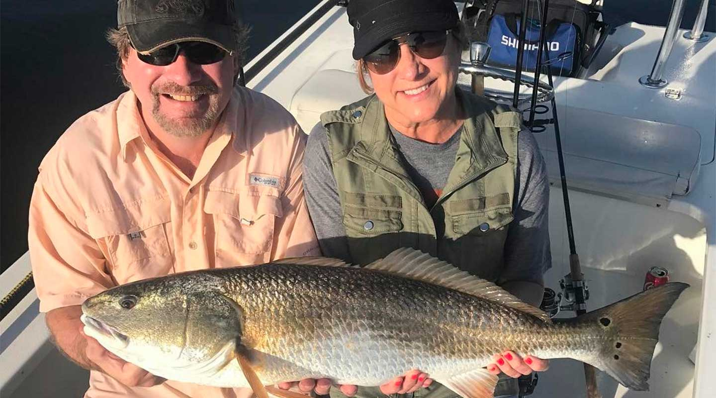 A couple holding bull redfish at the Inshore Fishing Charter