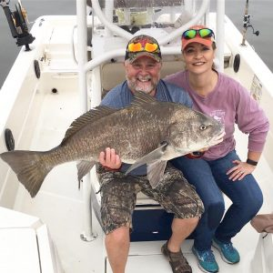 Cocoa Beach couple holding large caught fish on charter boat